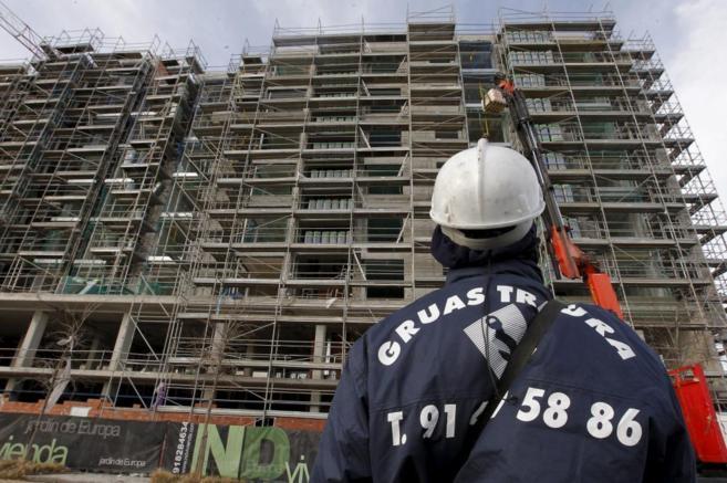 Un trabajador de la construcción observa el desarrollo de un edificio...