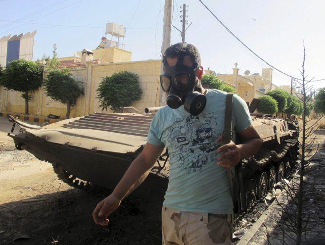 Un miembro del Ejéricto Libre Sirio, con máscara antigas, pasa junto...