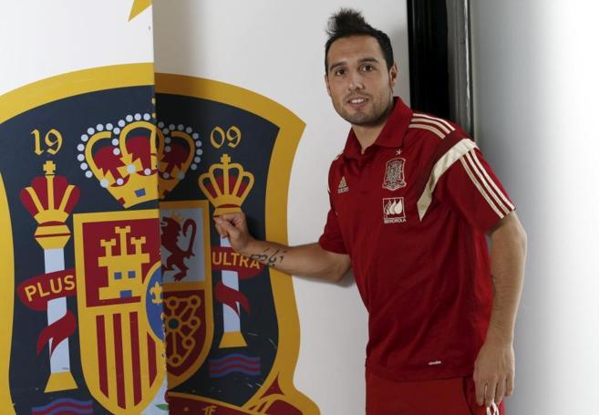 Cazorla posa junto al escudo de la Selección Española.