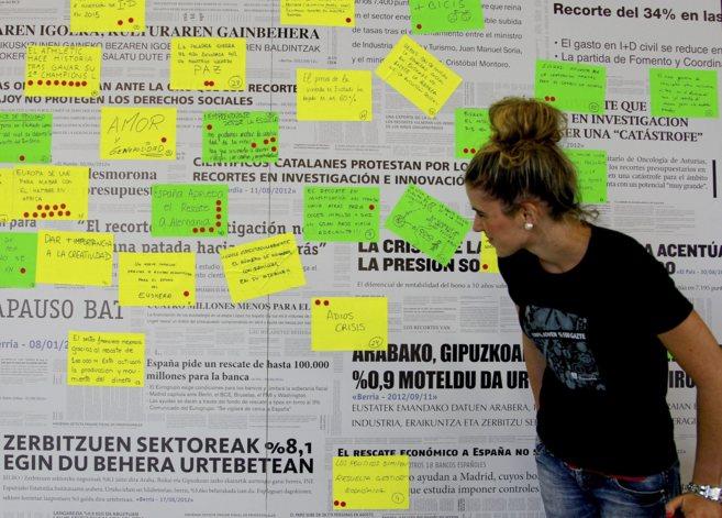 Una joven consulta un panel  en una feria de empresas  en Bilbao.