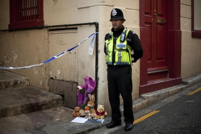 Un policía, junto a recuerdos en homenaje a las víctimas, cerca de...