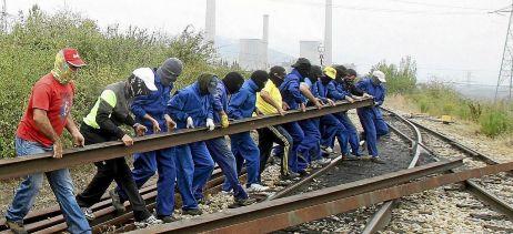 Un grupo de mineros haciendo un piquete a las puertas de una...