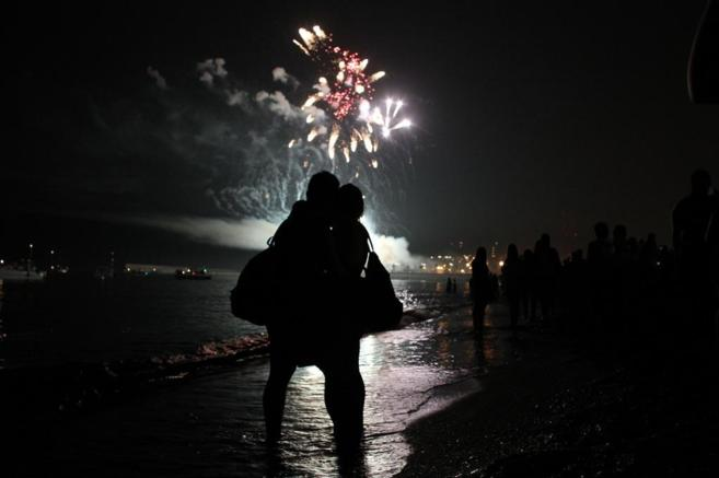 Una pareja observa unos fuegos artificiales desde la playa.