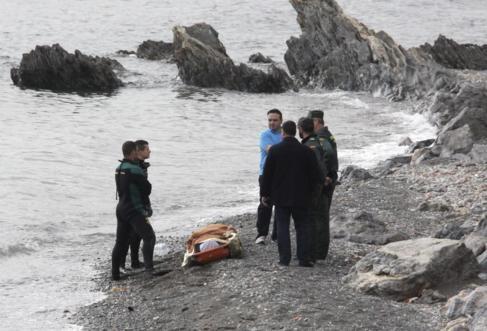 Miembros de la Guardia Civil con el cadáver de un inmigrante.