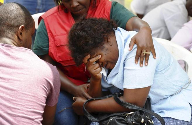 Un asistente de Cruz Roja atendiendo a un familiar de una de las...
