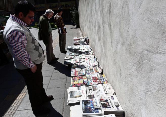 Iraníes observando los periódicos del día con las diversas...