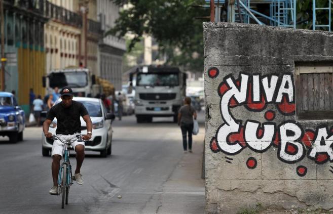 Un hombre pasa en bicicleta junto a una pintada, en una calle de La...