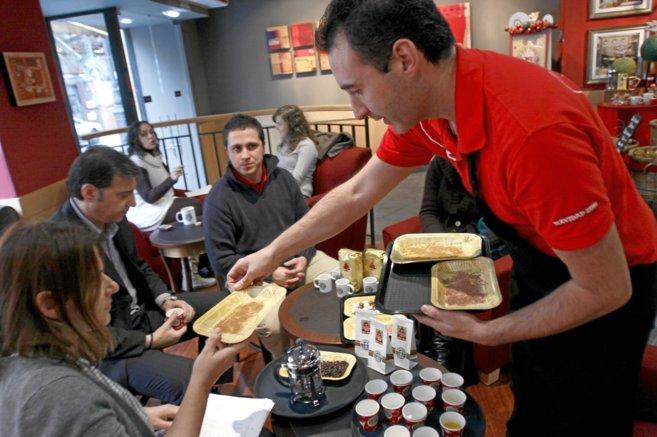 Un trabajador de Starbucks atiende a unos clientes en una de la...