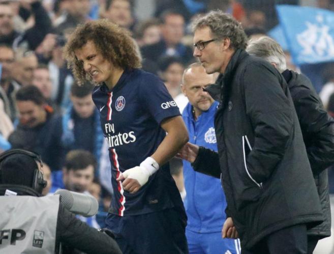 David Luiz, retirándose lesionado durante el partido contra el...