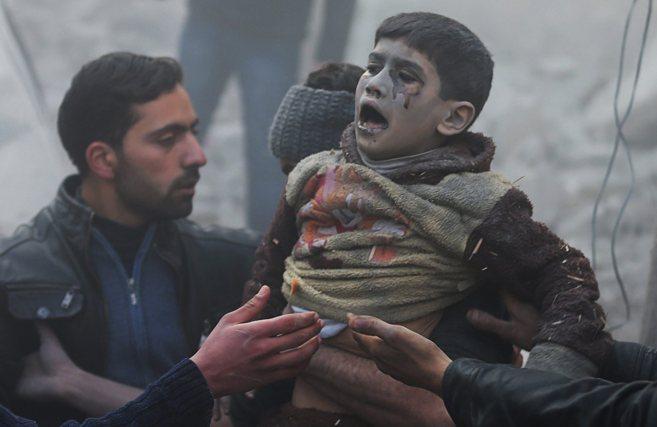Dos hombres ayudan a un niño herido durante un bombardeo de las...