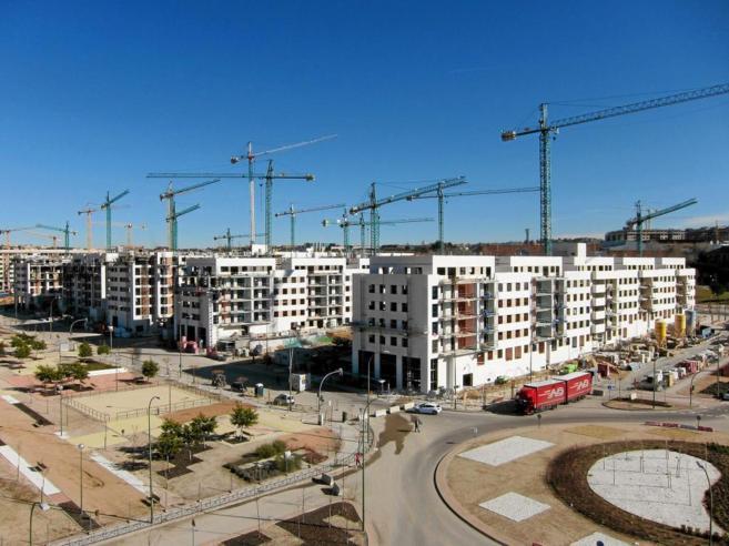 Vista de varias grúas trabajando en la edificación de viviendas en...