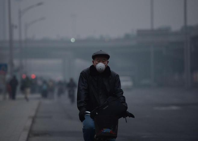 Un hombre monta en bicicleta con una máscara a causa de la polución...