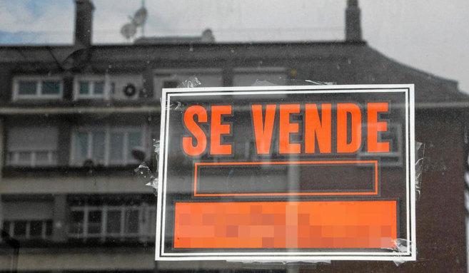 Cartel de 'Se vende' colgado sobre la ventana de una...