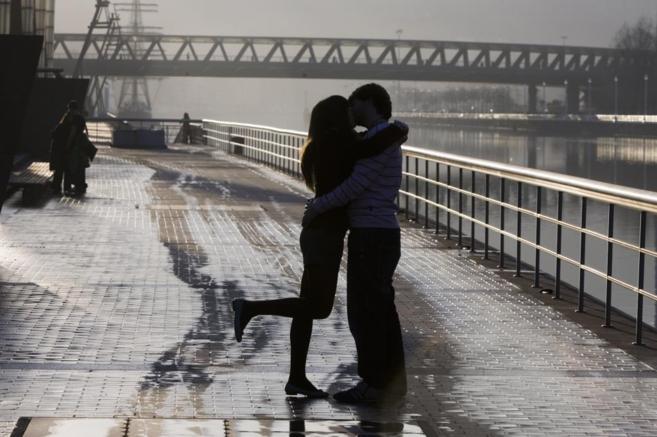 Una pareja se besa en el puente de Abandoibarra, en Bilbao.