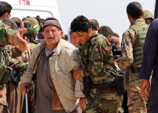 Un soldado peshmerga ayuda a un anciano tras ser liberado por el...