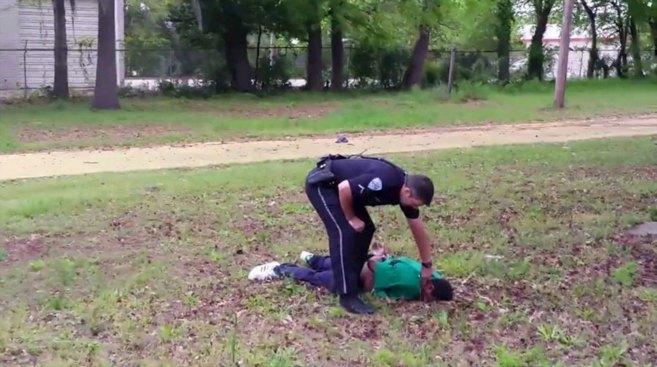 El oficial de policía Michael Slager junto a Walter Scott, caído a...