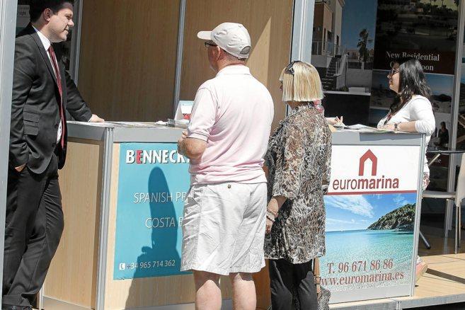 Un agente de ventas atiende a unos clientes extranjeros en unA feria...
