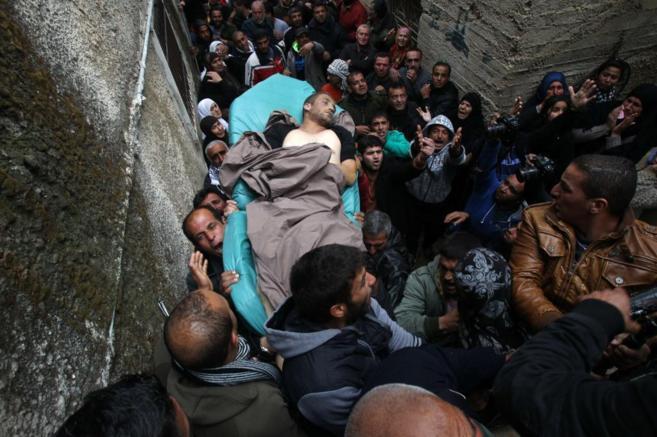 Parientes de Ziad Awad cargan su cuerpo por las calles de Beit Omar.