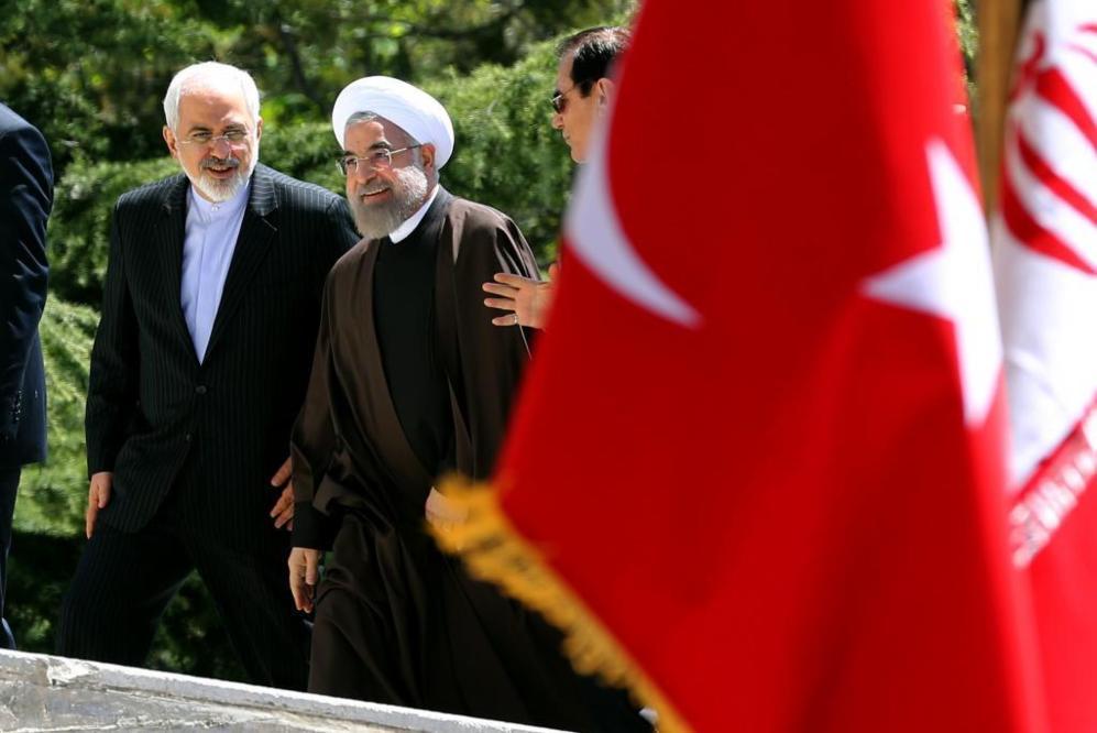 El presidente de Irán, Hasan Rohani (dcha.) conversa con su ministro...