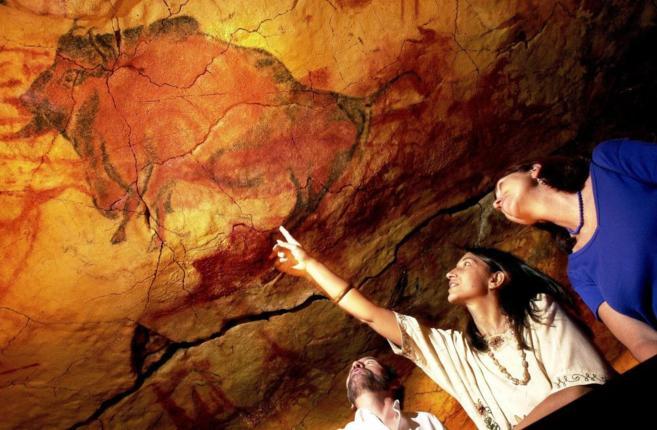 Dos turistas observan las pinturas de la cueva de Altamira.