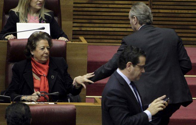Rita Barberá se saluda con el presidente Fabra en su escaño de las...