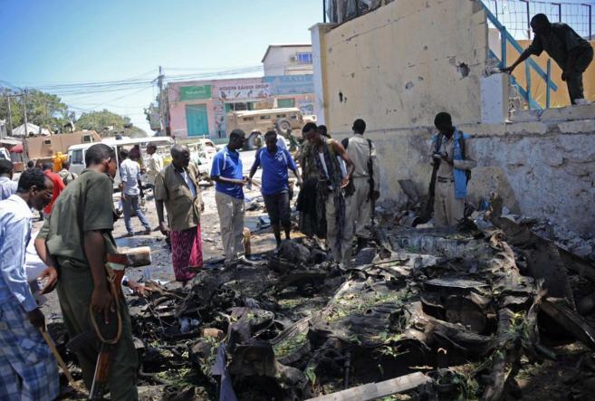 Personas miran los restos de un coche bomba frente al Ministerio de...