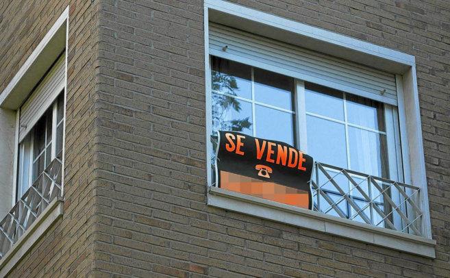 Un piso exhibe un cartel de 'Se vende' en la ventana.