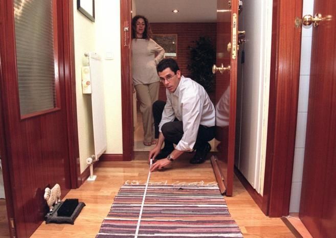 Un técnico efectúa una tasación inmobiliaria en el pasillo de una...