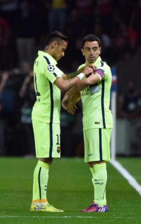 Neymar le pone el brazalete de capitán a Xavi en París.