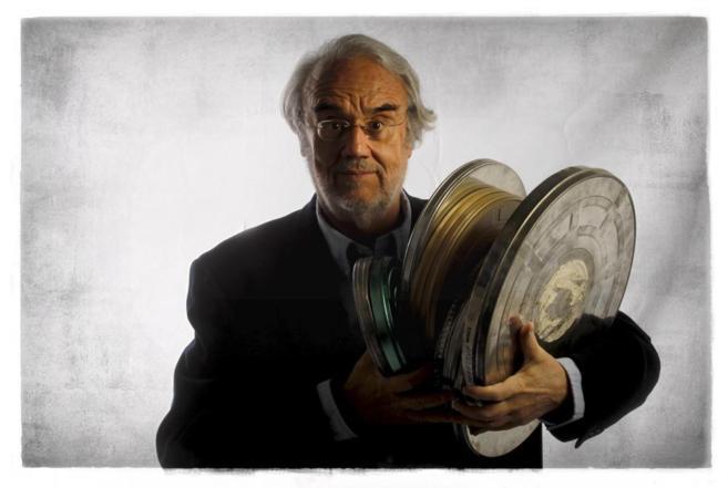 Manuel Gutiérrez Aragón posa con una pila de bobinas con películas.