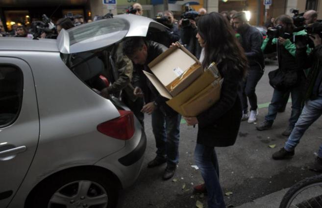 Agentes de la Policía trasladan cajas tras el registro en la vivienda...