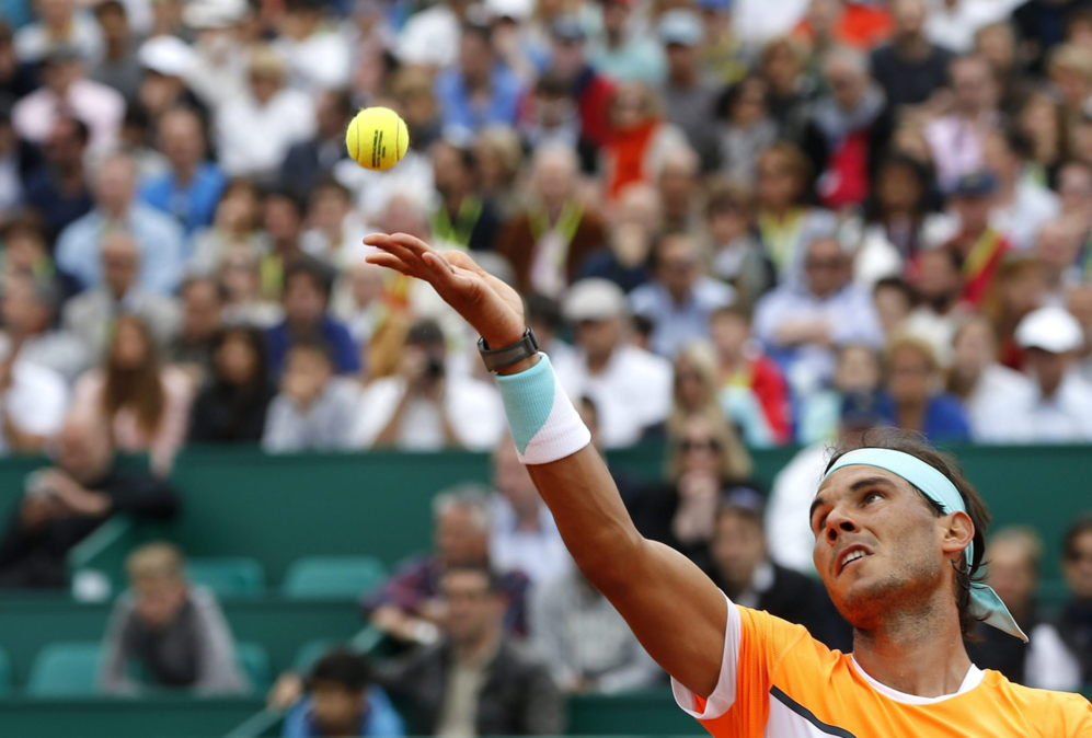El tenista español Rafael Nadal realiza un saque ante el francés...