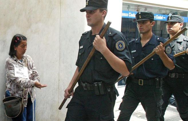 Una mujer pide limosna mientras pasan policías que desalojan a...