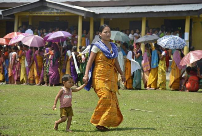 Una mujer con su hijo camina junto a una cola en las elecciones...