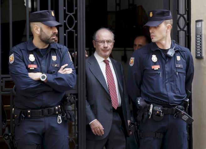 El ex vicepresidente del Gobierno, Rodrigo Rato, sale escoltado de su...