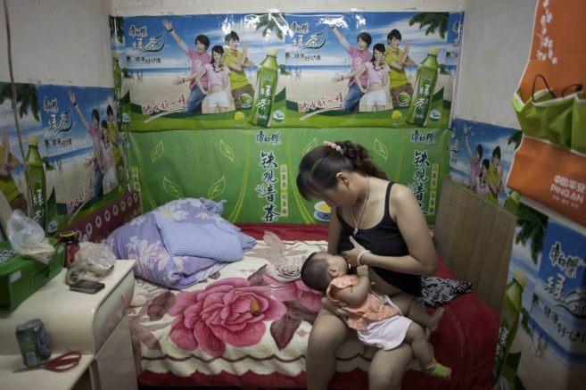 Zhou Limei amamanta a su bebé de ocho meses en su habitación bajo...