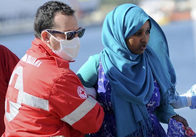 Una inmigrante es ayudada a desembarcar en el puerto de Palermo.