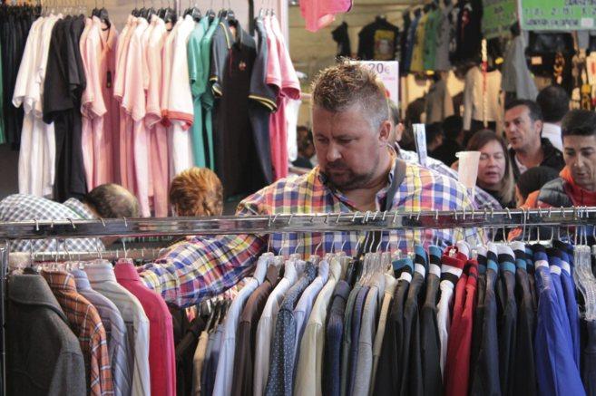 Un hombre busca ropa En Stock! Feria Outlet.