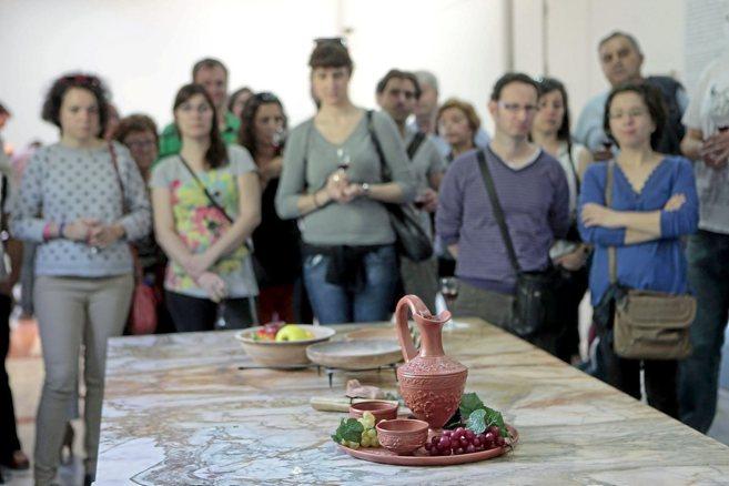 Los visitantes observan la reproducción de las vasijas que se...