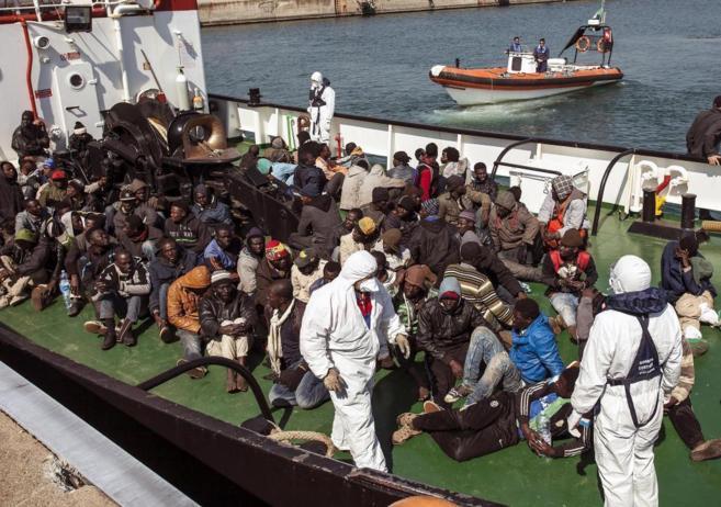 Un grupo de inmigrantes desembarcan en la costa italiana.