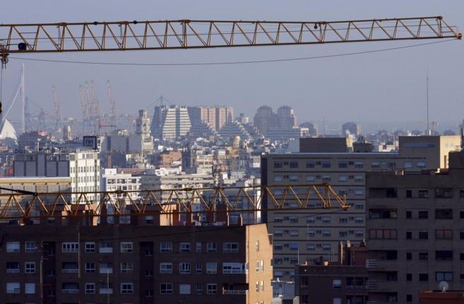 Panorámica de la ciudad de Valencia con varias grúas en primer...