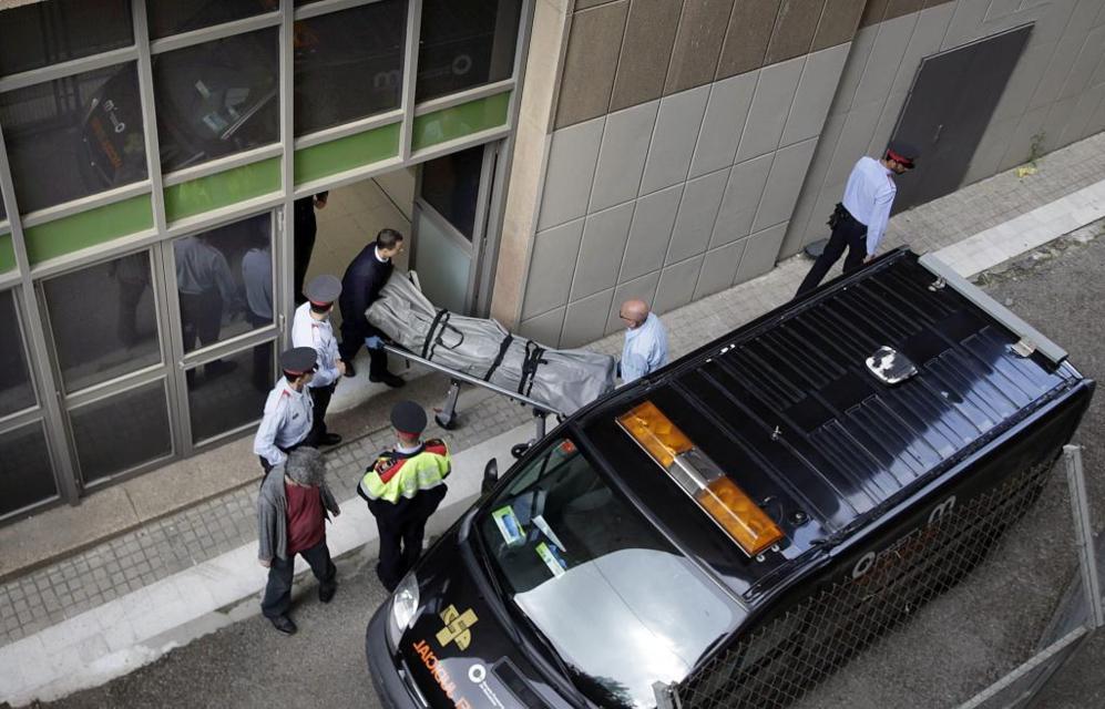 Personal de los Servicios Funerarios trasladan el cadáver del...