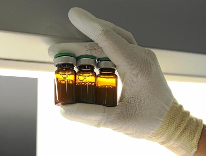 Un sanitario muestra varios viales de una vacuna contra la gripe.