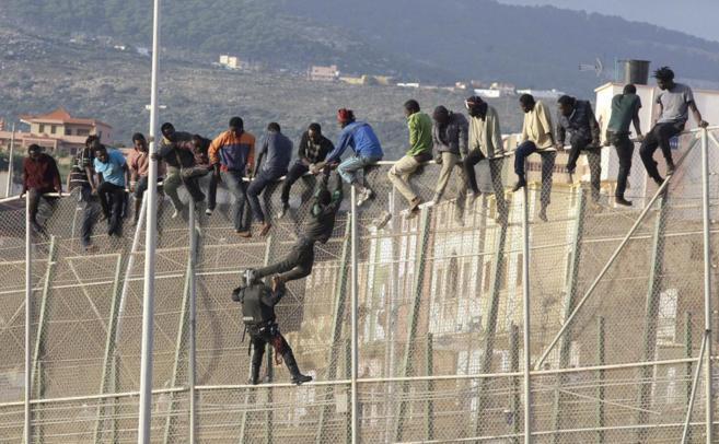 Un guardia civil actúa en la valla de Melilla con varios inmigrantes...