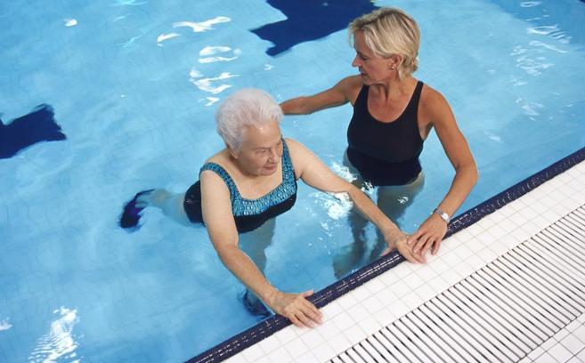 Una mujer realiza actividad física en una piscina.
