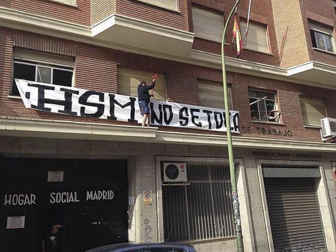 Uno de los 'okupas' en Chamberí coloca una pancarta en la...