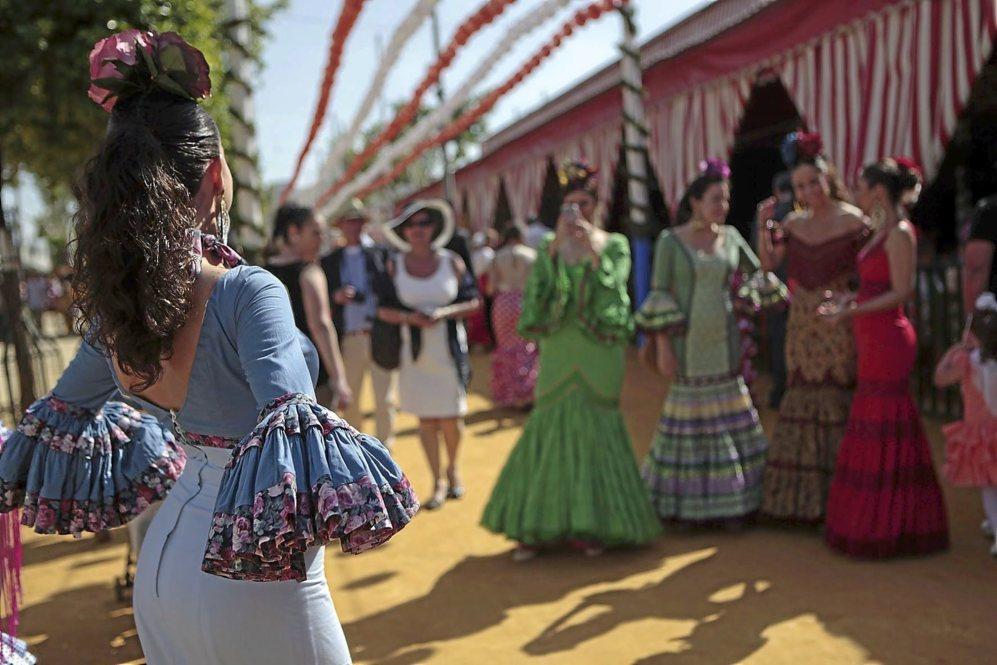 Una joven vestida de flamenca posa en el real mientras es fotografiada...