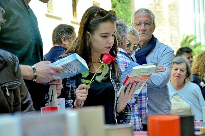 Una joven observando los ejemplares de un puesto del centro de la...