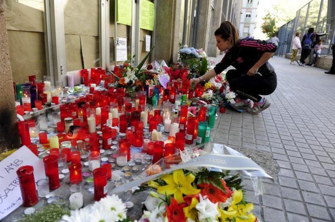 Velas y flores en la entrada del IES Joan Fuster del barrio de Navas...
