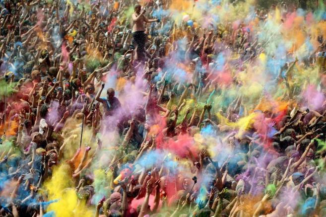 Miles de personas se lanzan polvos de colores, símbolo de alegría y...
